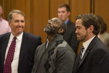Ricky Jackson, 57, of Cleveland, center,with lawyers Mark Godsey, left, and Brian Howe, looks skyward after being released from his life sentence for a 1975 murder, by Cuyahoga County Common Pleas Judge Richard McMonagle, Friday, Nov. 20, 2014 in Cleveland. The dismissal came after the key witness against Jackson and brothers Wiley and Ronnie Bridgeman recanted last year and said Cleveland police detectives coerced him into testifying that the three killed businessman Harry Franks the afternoon of May 19, 1975.  (AP Photo/Phil Long)
