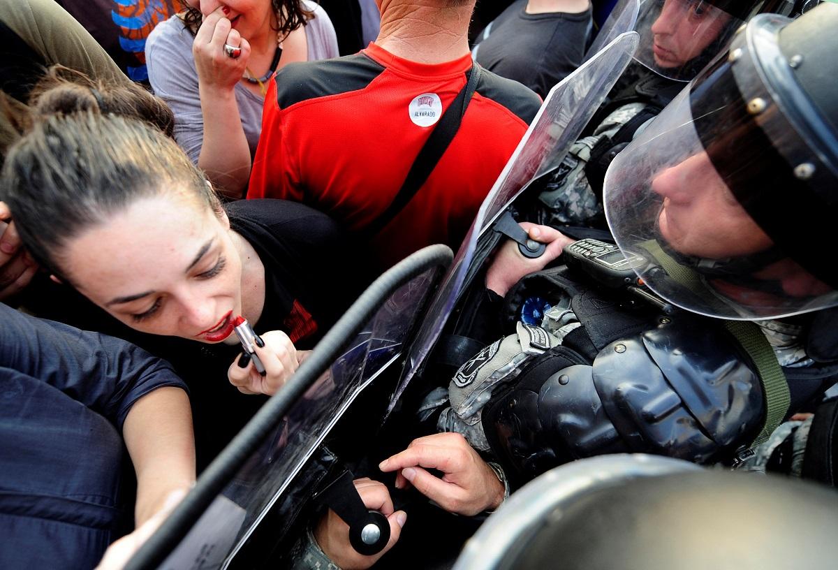 Η Jasmin Golubovska φορά το κραγιόν της και φιλά ασπίδα ΜΑΤατζή, σε διαδήλωση κατά της αστυνομικής βίας. Σκόπια, Βόρεια Μακεδονία, 2016.  Φωτογράφος: Ognen Teofilovski