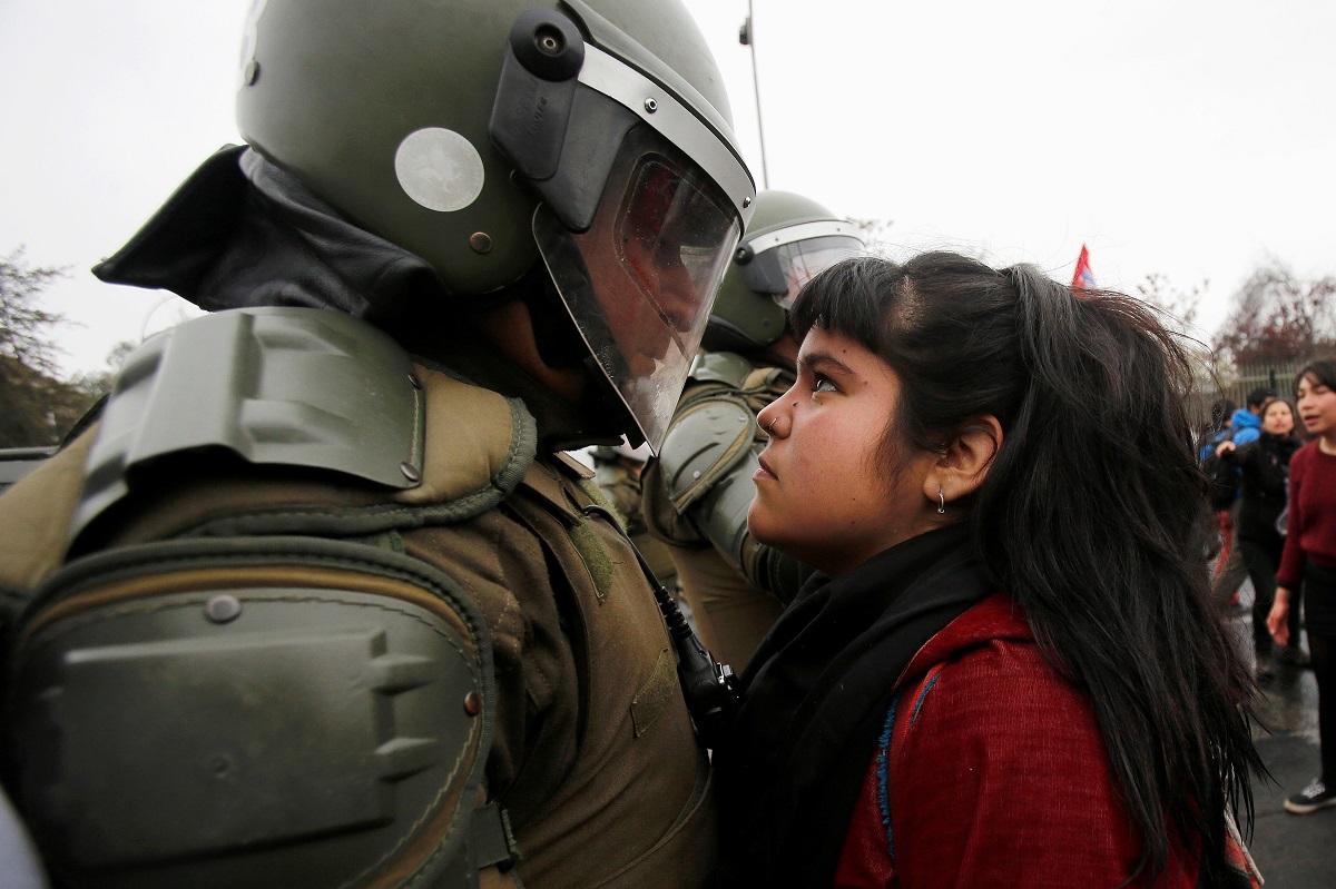 Μια γυναίκα, υψώνει το ανάστημά της απέναντι στην αστυνομική κατοχή στο Σαντιάγκο, στη Χιλή, το 2016. Φωτογράφος: Carlos Vera Mancilla