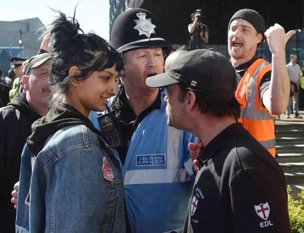 """Η Saffiyah Khan μπροστά σε έναν ρατσιστή, μέλος του EDL, που συμμετείχε σε """"παρέλαση"""" στο Μπέρμινχαμ, στην Αγγλία, το 2017. Φωτογράφος: Joe Giddens"""
