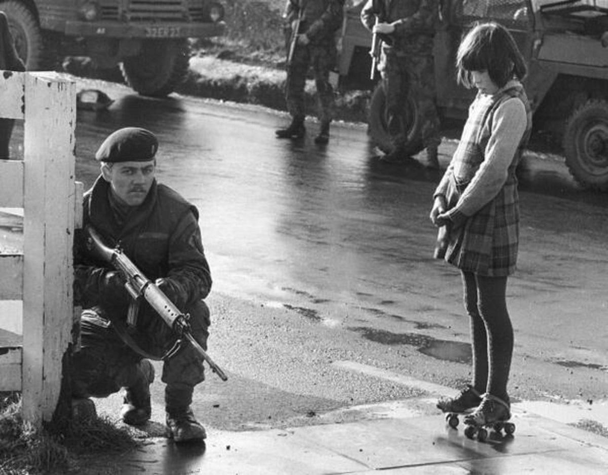 Μια νεαρή με ρόλλερ σκέιτ, περίεργη, πλάι σε έναν στρατιώτη. Ντέρυ, Βόρεια Ιρλανδία, 1969. Φωτογράφος: Clive Limpkin