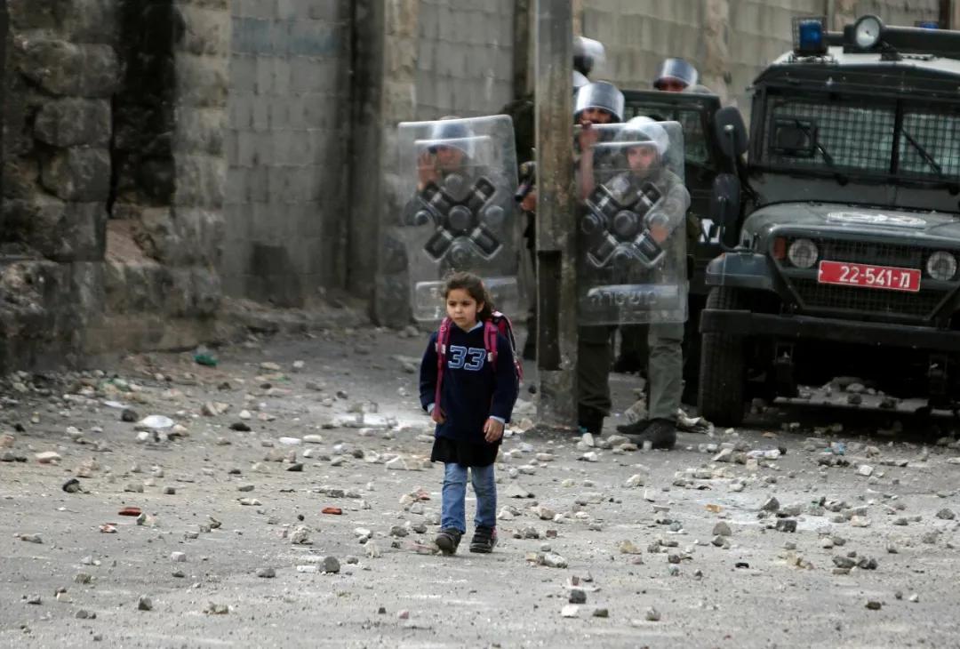 Μια μικρή, Παλαιστίνια μαθήτρια, επιστρέφει σπίτι της από το σχολείο, στη Δυτική Όχθη, δίπλα στην Ιερουσαλήμ.