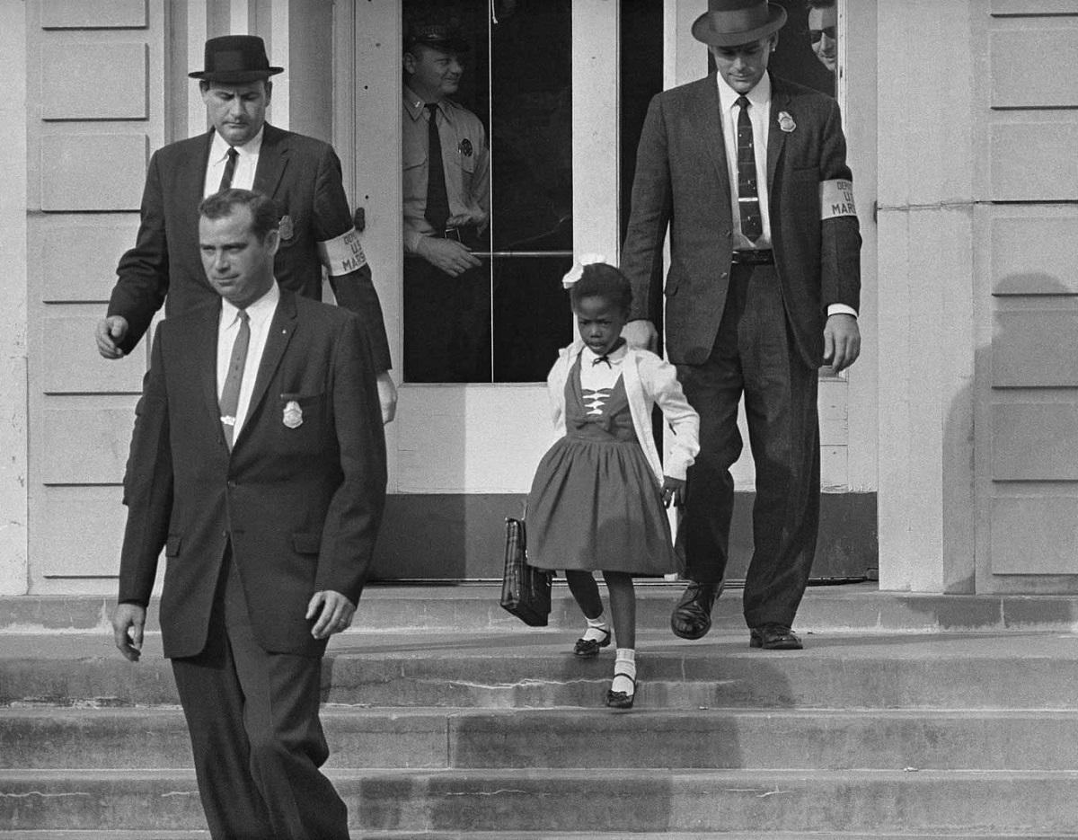 Η διάσημη φωτογραφία της Ruby Bridges, στην ηλικία των 6 ετών, στα σκαλιά του σχολείου. Προστατεύεται από ομοσπονδιακούς αστυνομικούς απέναντι σε ρατσιστές που δεν επιθυμούσαν τα έγχρωμα παιδιά στην εκπαίδευση. Νέα Ορλεάνη, Ηνωμένες Πολιτείες Αμερικής, πίσω στο 1960.