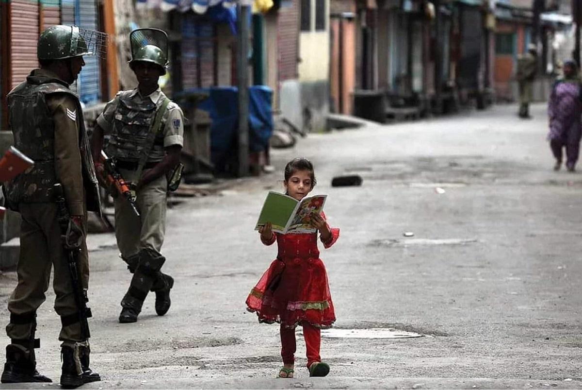 Μια πιτσιρίκα από το Κασμίρ, αγνοεί την απαγόρευση κυκλοφορίας. Δεν αφήνει τους βαριά οπλισμένους στρατιώτες να την ενοχλήσουν. Κυκλοφορεί ανενόχλητη, με το σχολικό της τετράδιο. Ινδία, 2016. Φωτογράφος: Ashish Sharma