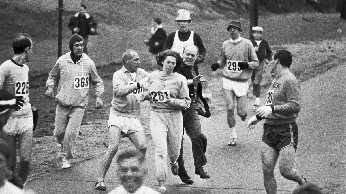 Η Kathrine Switzer, η πρώτη γυναίκα που επισήμως έτρεξε στον Μαραθώνιο της Βοστόνης. Στην φωτογραφία, παρενοχλείται από άντρα της διοργάνωσης που επιθυμεί να παραμείνουν οι αθλητικοί αγώνες, αντρική υπόθεση. Ηνωμένες Πολιτείες, 1967. Ο σύντροφος της Kathrine Switzer και άλλοι δρομείς, έδιωξαν τον άντρα και την προστάτευσαν φτιάχνοντας μία ανθρώπινη ασπίδα γύρω της για τον υπόλοιπο αγώνα.