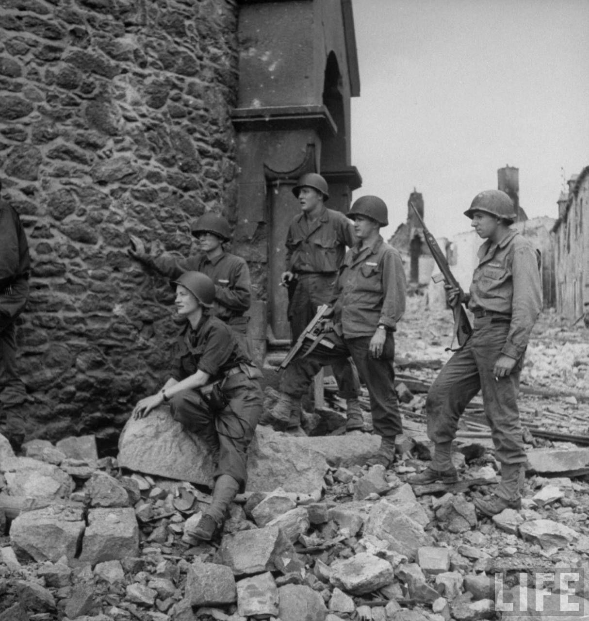 Η φωτογράφος Lee Miller κάθεται ανάμεσα σε Αμερικάνους στρατιώτες, στη Γαλλία, το 1944. Αγνόησε όλα τα πρωτόκολλα ασφαλείας και έγινε η πρώτη γυναίκα φωτογράφος στο ελεύθερο Παρίσι του Δευτέρου Παγκοσμίου Πολέμου.  Φωτογράφος: David E Scherman